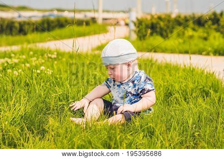 Cute Little Toddler Baby Boy Child Playing In The Park On Grass At Day Time. He Having Fun On The Ga