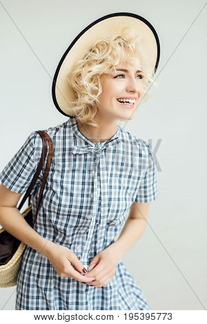 Happy girl with white hair in a hat and with a bag on her shoulder