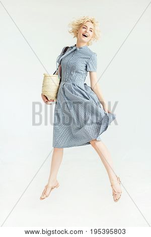 Blonde happy girl in a blue dress with a bag on a white background