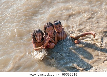 ROYAL RESERVE, CHITWAN, NEPAL. 28 September 2008: Young girls and boys Nepali Tharu tribe bathing naked in the Rapti river. Royal reserve  Chitwan, Nepal.