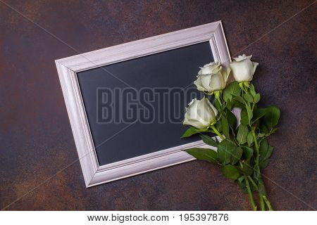 Black Chalk Board And White Roses On A Brown Background, Copyspace, Horizontal