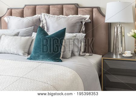 Classic Bedroom Style With Set Of Pillows And Lamp On Table Side
