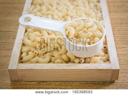 Food and Cuisine Uncooked and Dried Elbow Macaroni or Gomiti Pasta in Plastic Measuring Cup.