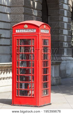 Red telephone booth on the street in the city London United Kingdom.The red telephone box( telephone kiosk) is one of the symbols of UK used since about 1920