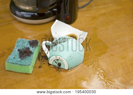 A broken cup sponge spilled coffee next to the coffee machine on a table top