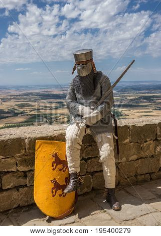 Medieval knight on guard at the entrance of a castle, at rest, resting, reenactment with costumed characters and medieval armor with chainmail, helmet swords and shields. Medieval demonstration and recreation