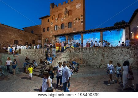 Certaldo Tuscany Italy - July 13 2017: The Palazzo Pretorio whit his picturesque facade adorned with ceramic coats of arms the clock tower and the loggia whit blue light