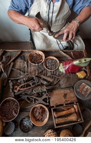 The shoemaker at his work bench. Various tools and instrument are placed on the work bench