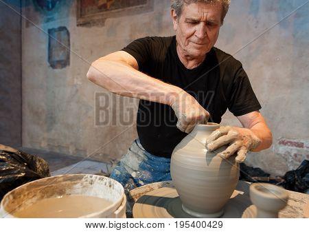 Certaldo Tuscany Italy - July 13 2017: Old artisan maestro making clay pot terracotta on the pottery wheel at