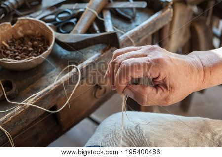 The shoemaker prepares the string for sewing a shoe. Various tools and instrument are placed on the work bench