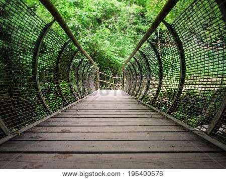Characteristic pedestrian wooden bridge with a metal grating parapet that resembles the shape of a tunnel.