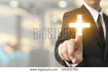 Businessman hand touching plus sign with blurred background Business offer positive benefit and development concept