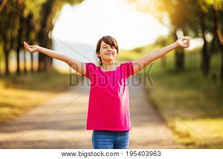 Beautiful little girl with her arms outstretched enjoys in nature.