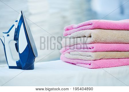 Iron And Heap Of Rose And Beige Towels