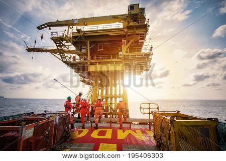 Offshore oil and gas platform during crew boat transfer worker to the platform during sunset time
