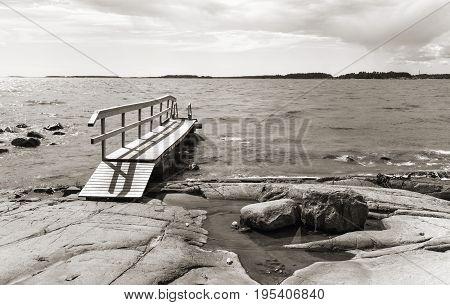 Small wooden foot bridge over rocks leads into the sea