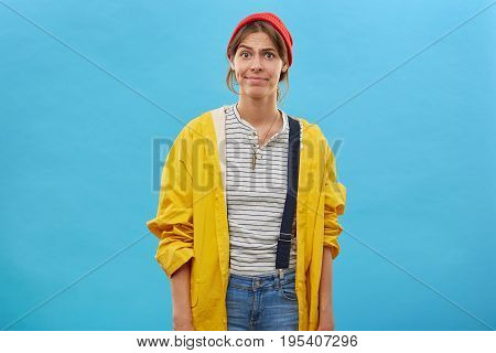 Portrait Of Dissatisfied Woman Wearing Red Hat, Yellow Raincoat And Overalls Frowning Her Face Havin