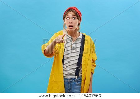European Woman With Surprised Expression Dressed In Yellow Casual Loose Jacket Pointing With Index F