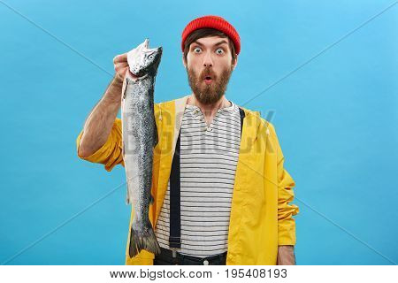 Attractive Male With Beard Dressed In Red Hat, Yellow Raincoat And Overalls Holding Huge Fish Lookin