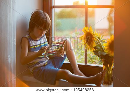 Cute Little Toddler Child, Playing With Abacus On A Window