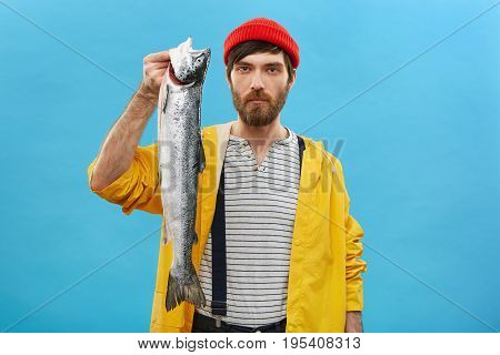 Bearded Young Man Angling Big Fish In Pond, Posing With It Over Blue Background Having Serious Expre