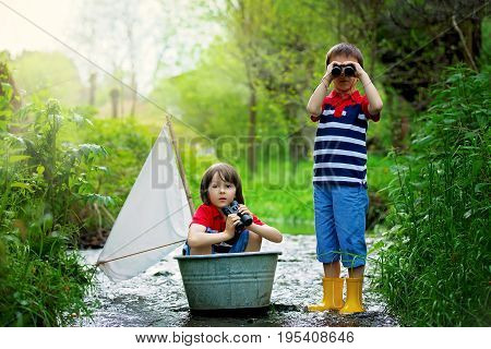 Cute Children, Boys, Playing With Boat On A Little River