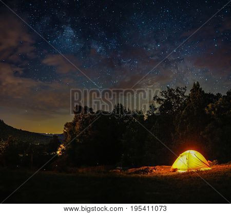 A camping tent is under milky way sky and twilight at night in Horseshoe Canyon Ranch, Jasper Arkansas.