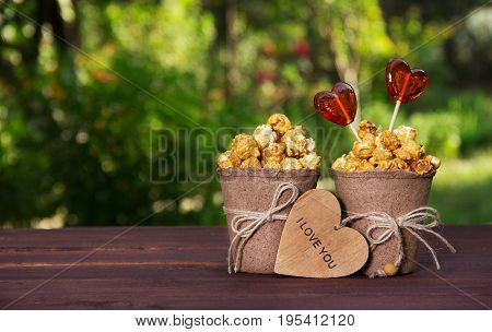Two paper buckets with popcorn and heart shaped lollipops. Romantic concept. Snack for movies