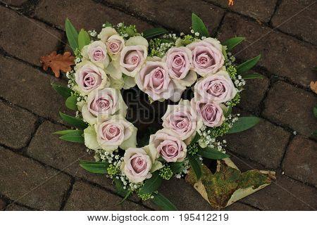Heart shaped purple sympathy flowers or funeral flowers near a tree