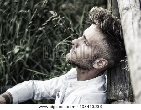 Blondish, blue eyed young man leaning on wood fence in grass lawn at sunset, thinking, looking away
