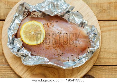 Raw chicken fillet with lemon slice black pepper and salt in baking foil. Uncooked chicken breasts on wooden cutting board