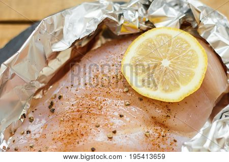 Raw chicken breast with lemon slice sea salt and grinded black pepper in baking foil. Uncooked chicken