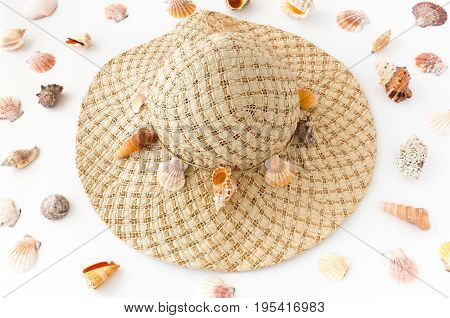 Home decorated woman straw hat with seashells surrounded by a variety of seashells on white background.