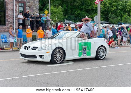 MENDOTA, MN/USA - JULY 8, 2017: Grand Marshal for the Mendota Days Parade rides in motorcade through main street of the historic city. Mendota is one of the first permanent settlements in Minnesota.