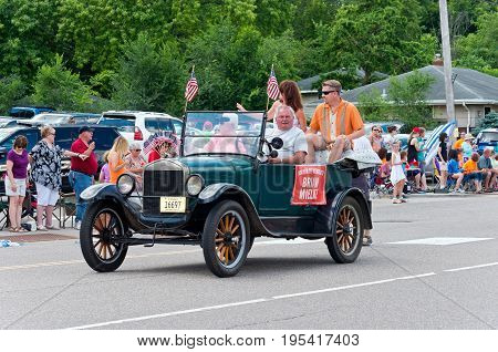 MENDOTA, MN/USA - JULY 8, 2017: The Mayor of Mendota rides in motorcade through main street of the historic city during annual parade.  Mendota is one of the first permanent settlements in Minnesota.