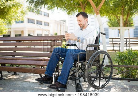 Man In Wheelchair Using A Smartphone