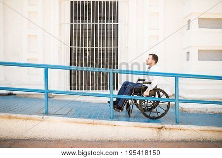 Man In Wheelchair Going Up A Ramp
