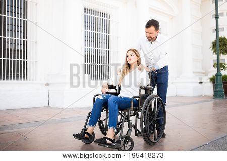 Man Comforting Girlfriend On A Wheelchair