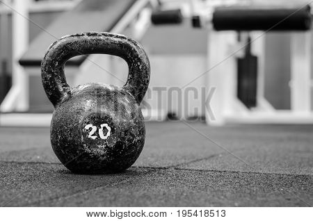 Kettle bell. Old and rusty Kettle Bell on the gym floor in black and white. With film grain.