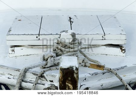 details of an old wooden boat anchored with a black rope