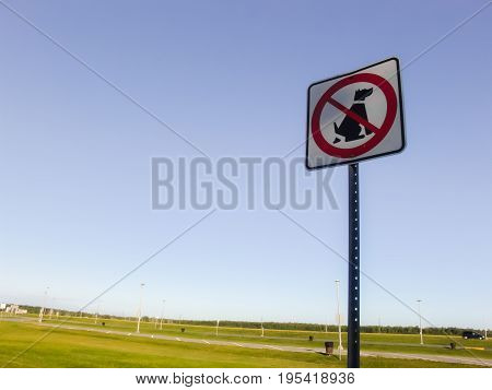No dog pooping sign on green grass against sky background