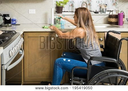 Woman In Wheelchair Cleaning The Kitchen
