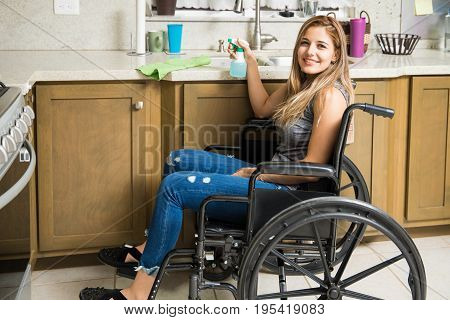 Happy Woman In Wheelchair Cleaning The House