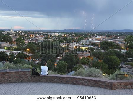 SANTA FE, NEW MEXICO, JULY 6. Fort Marcy Park on July 6, 2017, in Santa Fe, New Mexico. A Man Watches a Lightning Storm from Fort Marcy Park in Santa Fe.