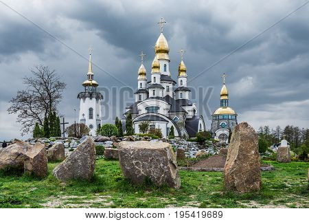 BUKI KIEV REGION UKRAINE - MAY 02 2015: The temple complex in a landscape park in the village Buki. Built by businessman Ivan Suslov. In the center is the Christian church of St. Eugene.