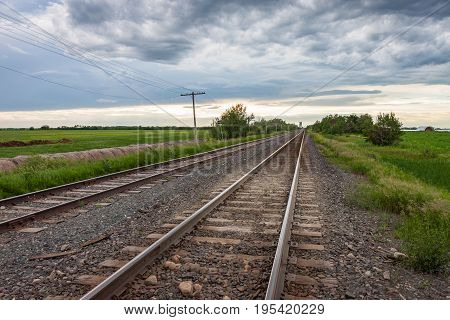 Two pairs of tracks on wooden ties leading to cloudy sky in Canadian prairie