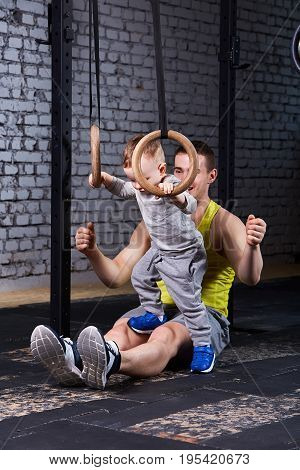 Happy father and little cute son exercising with rings against brick wall. Sporty man and child in the sportwear and sporty shoes. Child rearing in healthy lifestyle.