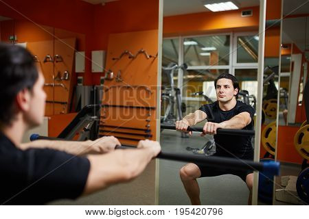 Young sporty man in the black sportwear with barbell doing squats in gym n front of the mirror. Athlete man in the t-shirt and shorts. Healthy lifestyle. Power and energy.