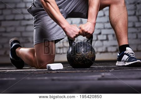 Close-up photo of young sportsman while crouching on a one leg and holding kettlebell against brick wall in the cross fit gym. Athletic man in the shorts and sporty shoes. Vertical photo. Healthy lifestyle. Detail of the sportsman.