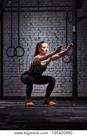 Young beautiful sporty woman making squats against brick wall in cross fit gym. Woman in the black sportwear, t-shirt, leggings and orange sporty shoes. Healthy lifestyle. Concept of the cross fit activity.
